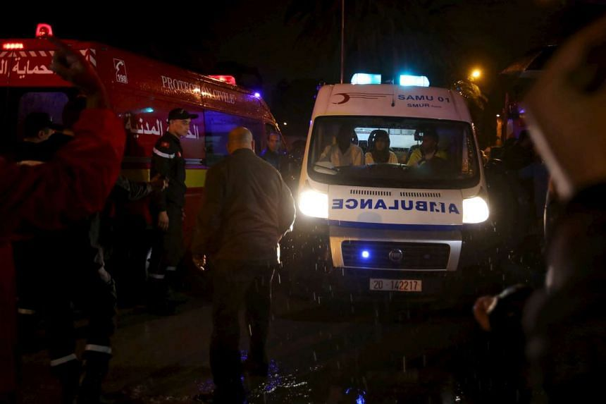 Police help to make way for an ambulance carrying bodies after an attack on a military bus in Tunis.