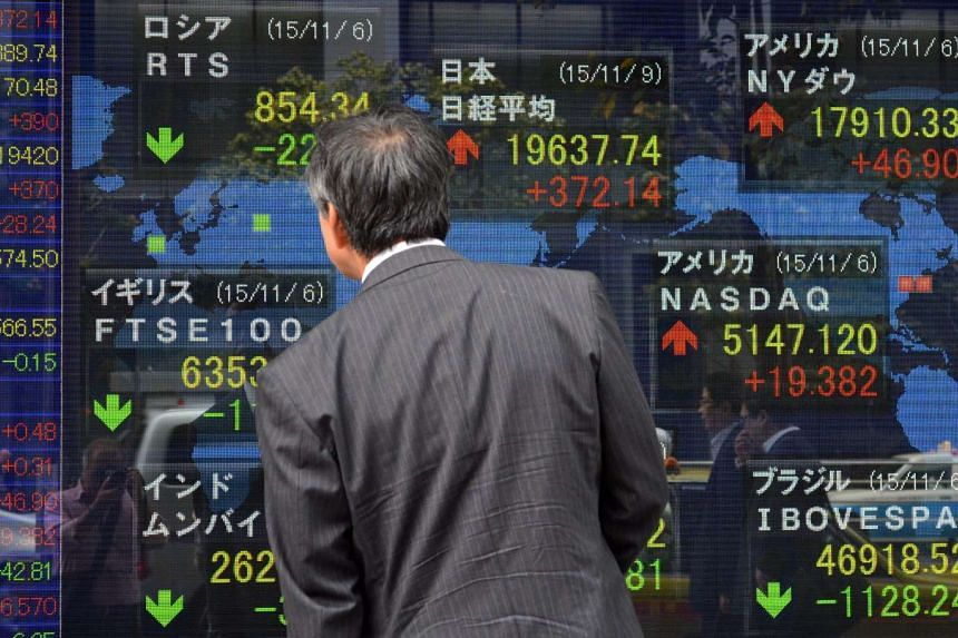A man looking at a share prices board in Tokyo on Nov 9, 2015.