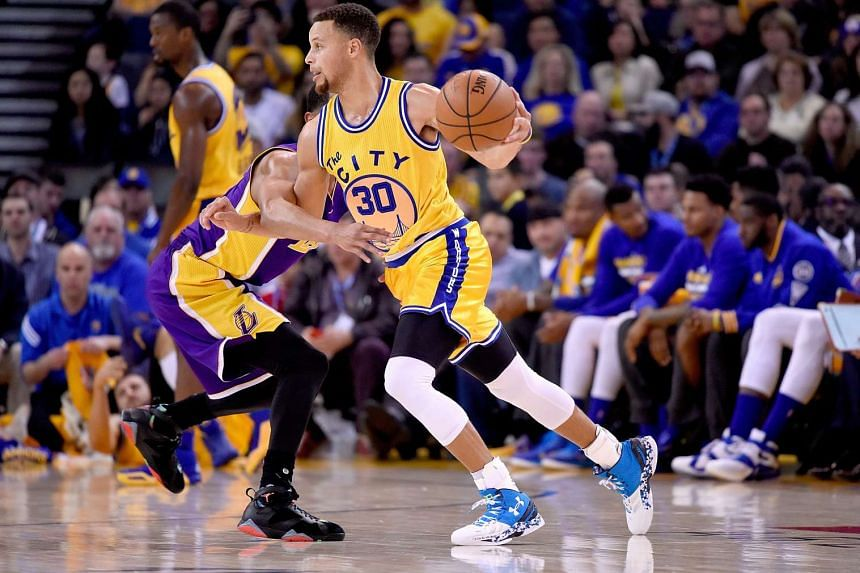 Stephen Curry #30 of the Golden State Warriors dribbles past Jordan Clarkson #6 of the Los Angeles Lakers during their NBA basketball game.