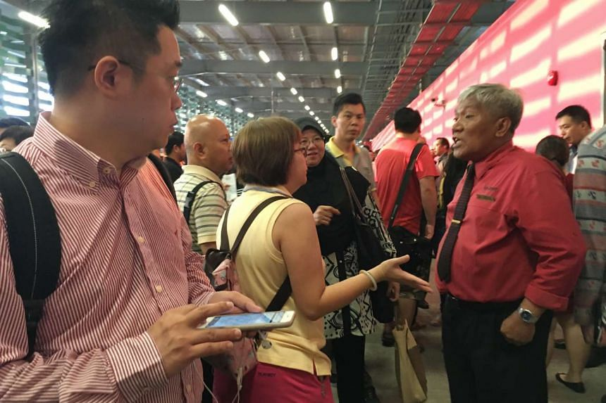 Commuters - at Yishun bus interchange - speaking to SMRT staff seeking alternative route suggestions.