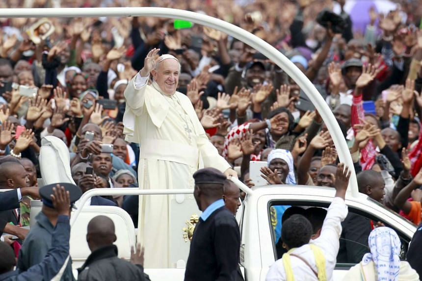 Pope Francis waves to faithful while riding in an open truck  in Kenya's capital Nairobi.