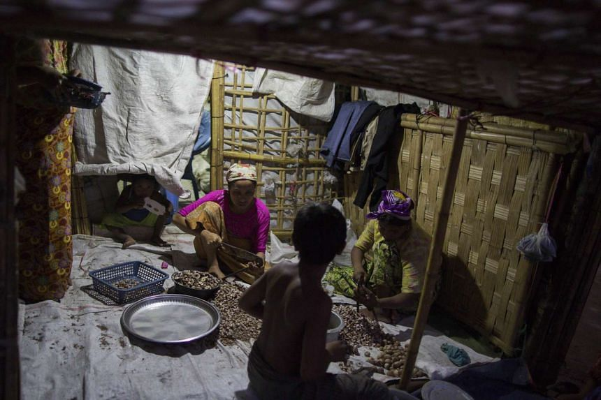 A Rohingya family selects beta to sell at their shelter at the Thel-Chaung displacement camp.