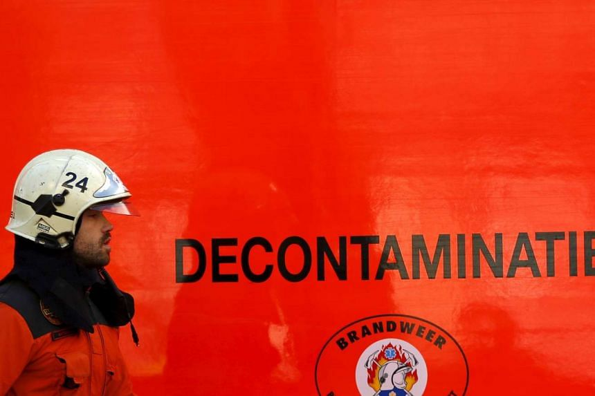 A Belgian firefighter walks past a truck of the decontamination unit outside the Grand Mosque in Brussels on Nov 26, 2015.