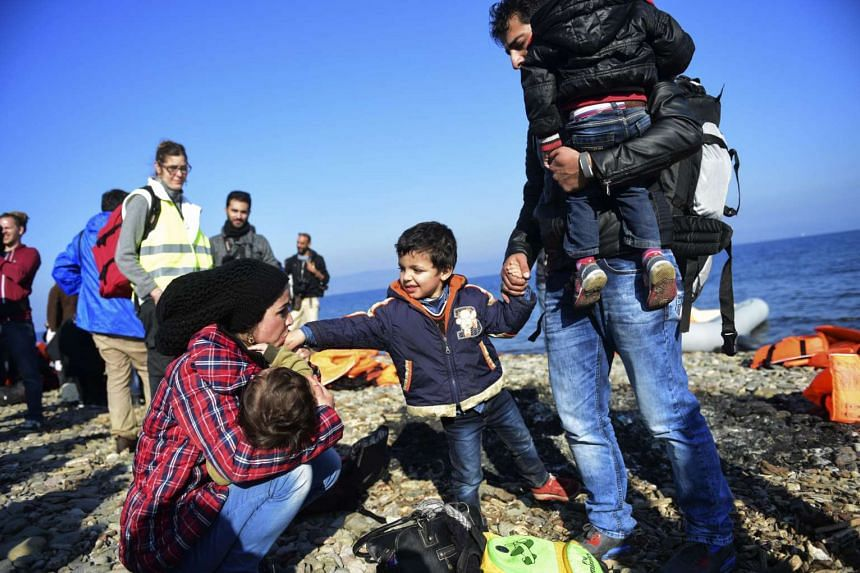 A Syrian family arrives on the Greek island of Lesbos from Turkey with other migrants and refugees.