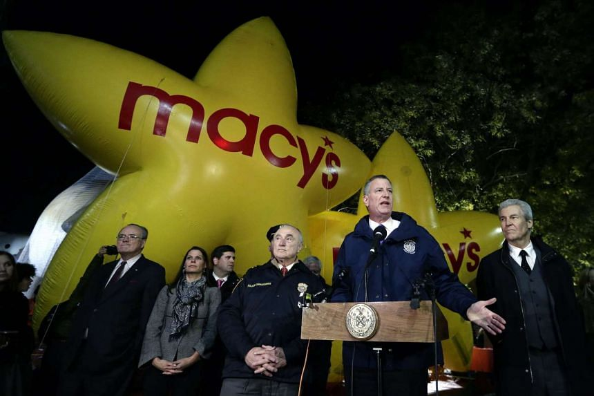 New York City Mayor Bill De Blasio (centre) talks to the media in front of the balloons during the Macy's 89th Annual Thanksgiving Day Parade in New York City, Nov 25, 2015.