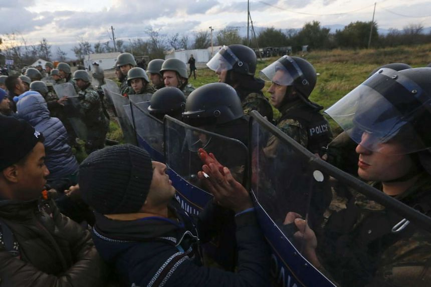 Migrants push a line of Macedonian police officers as they try to cross the Greek-Macedonian border near the Greek village of Idomeni on Nov 26, 2015.