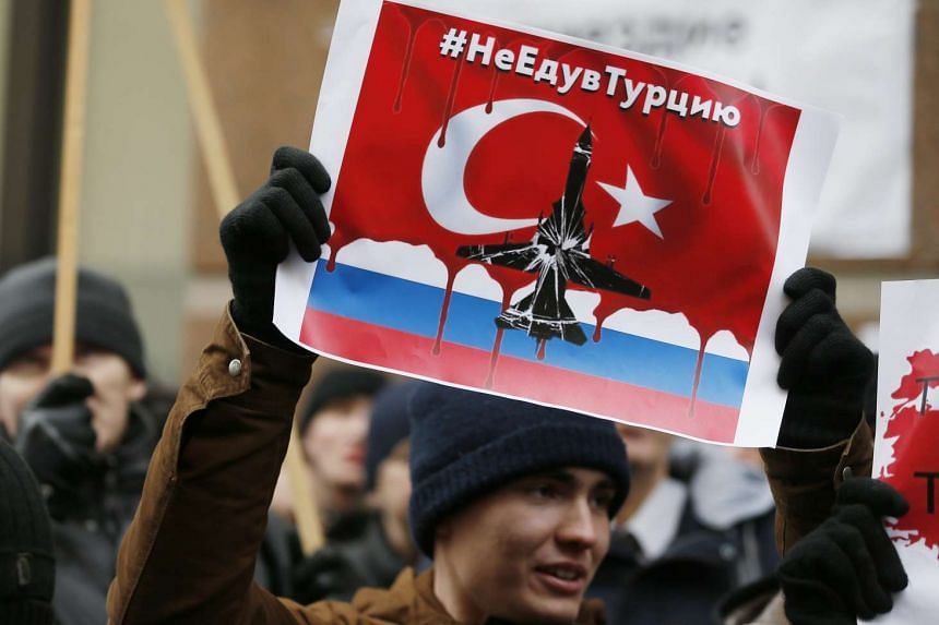 """A Russian protester holds a placard reading: """"Don't go to Turkey"""", as he takes part in a rally in front of Turkish embassy in Moscow, Russia, Nov 25, 2015."""