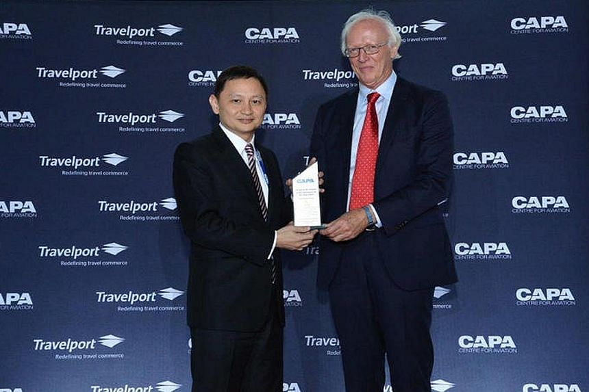 SIA chief executive Goh Choon Phong receiving his award from Centre for Aviation executive chairman Peter Harbison on Monday. Mr Harbison said that since Mr Goh took charge, SIA has made more major strategic changes than any full-service airline grou
