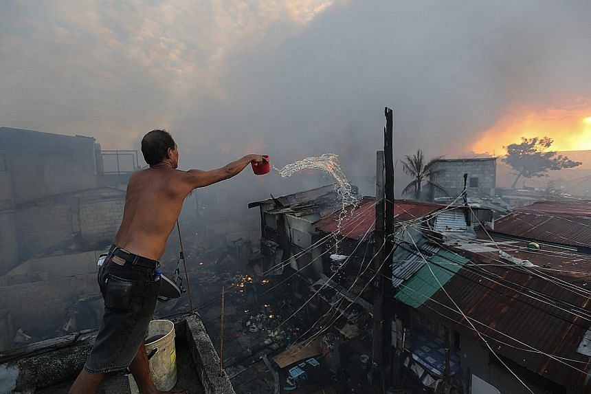Filipino Fil Binay battles to contain a fire in Mandaluyong City, east of Manila, yesterday. The cause of the fire, which reached the general alarm level, is still unknown.