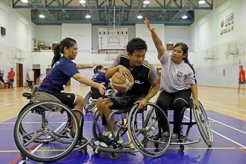 Mr Ng Chong Ping, 42, tries to shield the ball from volunteers Jeannette Leung (left), 25, and Nur Sahira, 24. The team train with a group of able-bodied volunteers, who prove to be tough opponents. Above: Mr Kamas Mohd, 44, gets a rebound while play