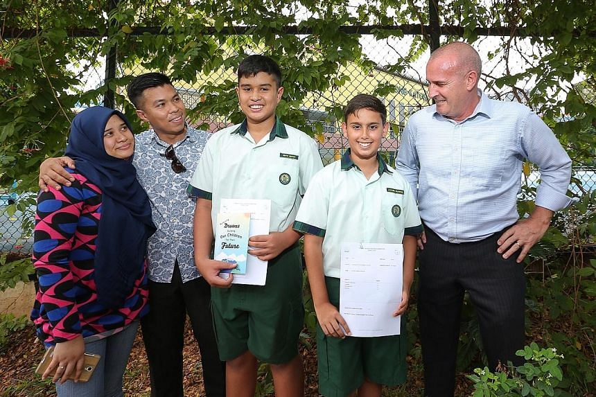 (From left) Madam Nur Aryana Aziz; her husband, Mr Sadri Farick; their son, Emyr Uzayr; Jayden Francis, and his father, Mr Dannie Francis, at Tanjong Katong Primary School yesterday.