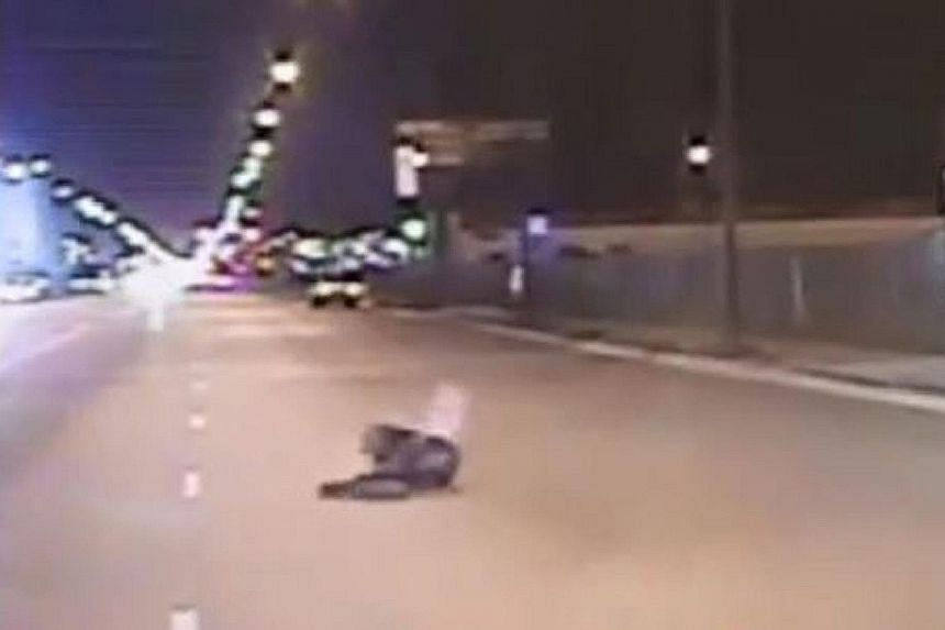 Video footage released by Chicago police shows (from left) teenager Laquan McDonald walking past police cars carrying a knife, then looking at the police before being shot, and on the ground after the shooting. Protesters took to the streets of downt