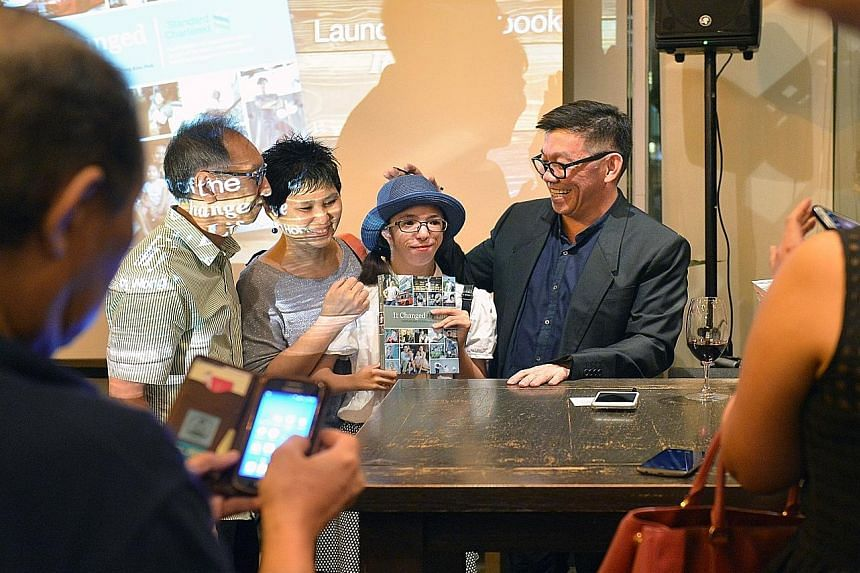 Straits Times senior writer Wong Kim Hoh posing for a photograph with one of his interviewees, photography student Isabelle Lim (second from right), and her parents Nick and Jacqueline Lim, at the launch of his latest book, It Changed My Life, yester