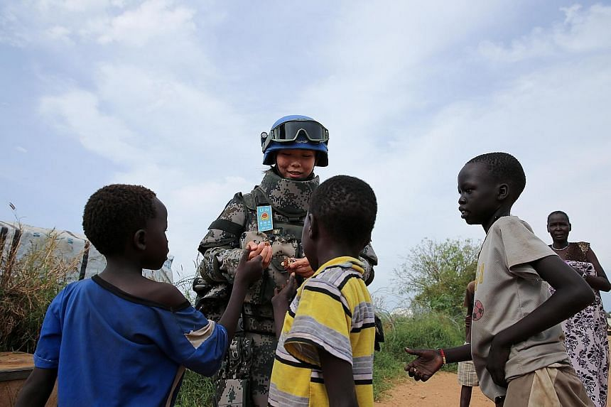 Chinese peacekeeper Jia Xiaochen hands out sweets to children in a refugee camp in Juba, South Sudan. China sent its first peacekeeping infantry battalion to South Sudan in April this year, consisting of 700 peacekeepers. The contingent, which also i