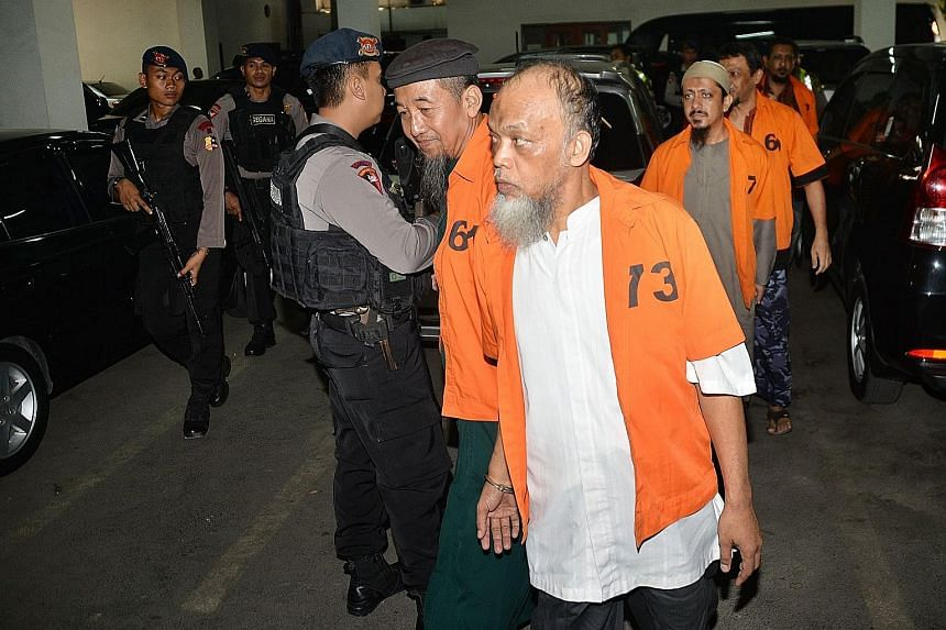 Muhammad Basri (front) and other terror suspects arriving for their trial on Oct 20. They are said to have links with ISIS.
