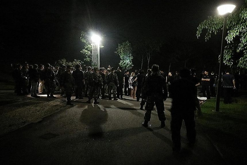 Police officers and men in army uniform on a stretch of Punggol Waterway Park, near Sentul Crescent, with the 13 men and eight women arrested for wilful trespass on state land on Tuesday evening.