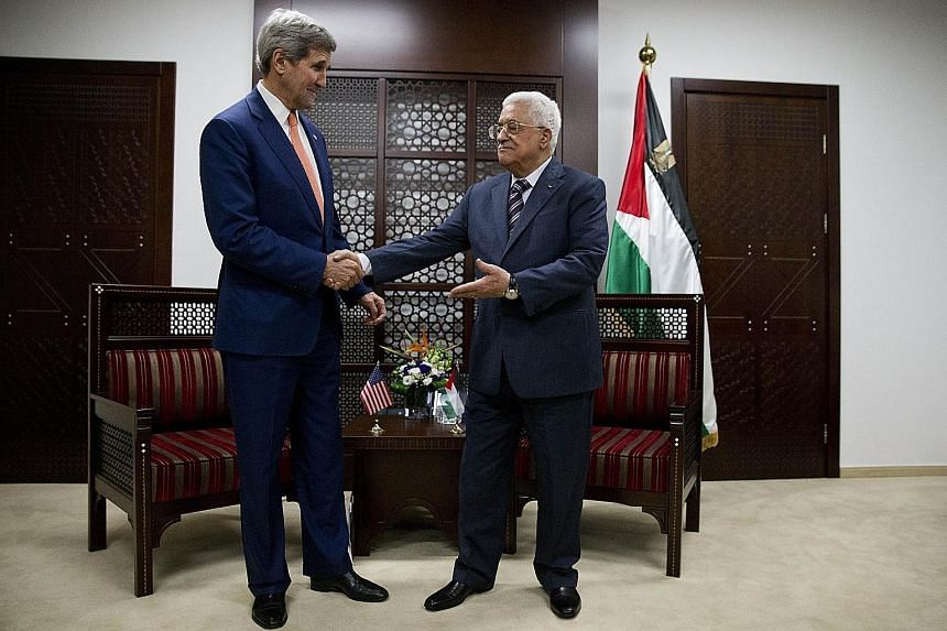 Mr John Kerry (left) meets Mr Mahmoud Abbas upon his arrival in the West Bank city of Ramallah on Tuesday.