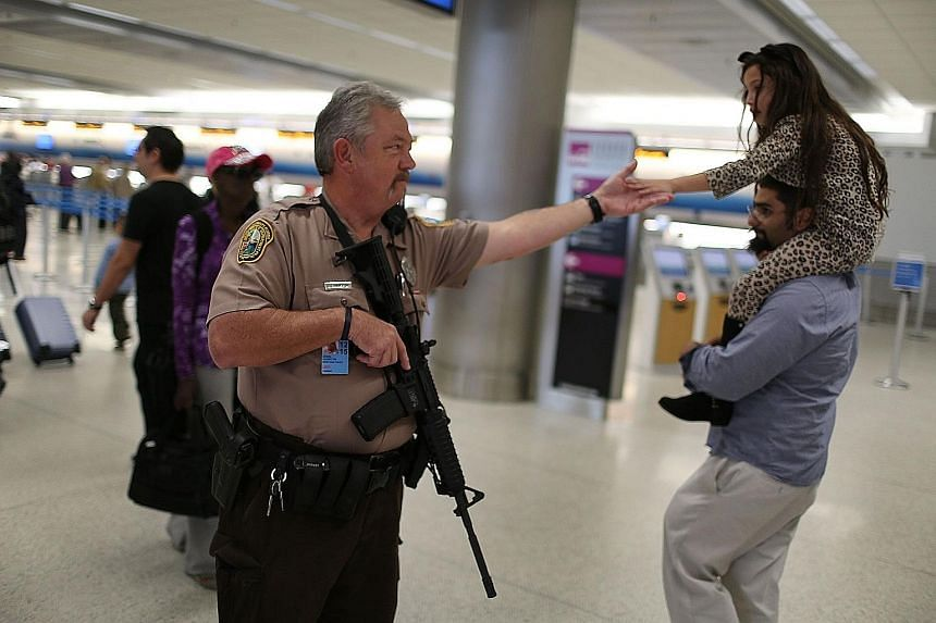 An officer on patrol at Miami International Airport. Many Americans are going ahead with their holiday plans.