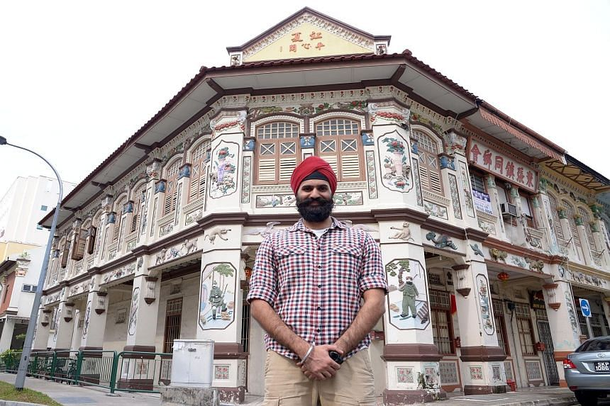 "Mr Ishvinder Singh, a co-developer of the Sikh Heritage Trail app, at a traditional shophouse in Lorong Bachok in Geylang, which has carvings of Sikh guards, designed to ""watch over"" the building."