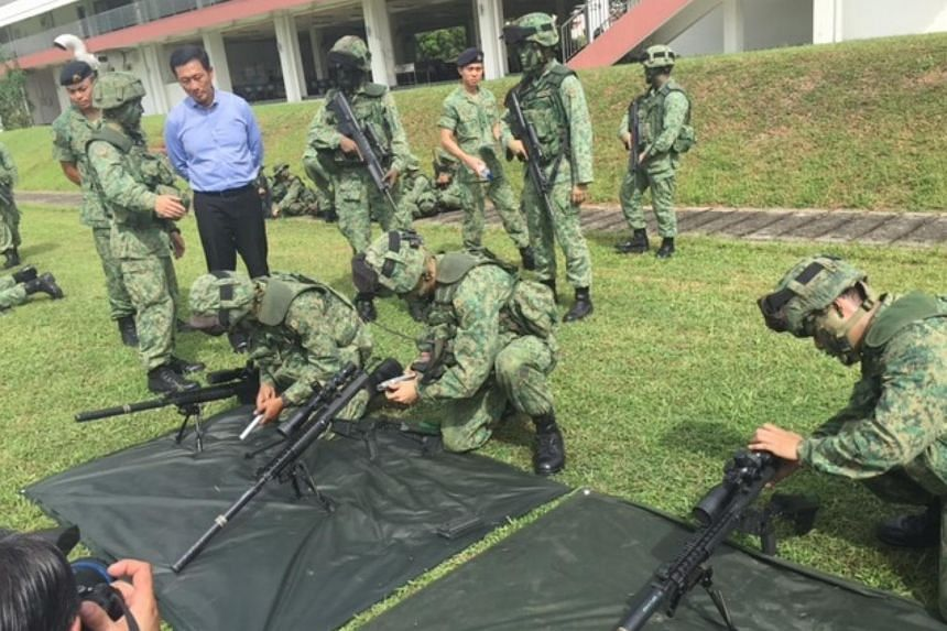 Senior Minister of State for Defence Ong Ye Kung (in blue shirt) watching soldiers from the 2nd Battalion Singapore Infantry Regiment (2 SIR) respond to a mock war scenario.