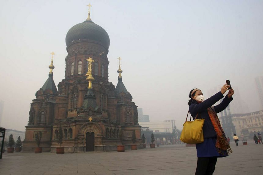 A woman posing for a selfie in front of Harbin's landmark San Sophia church, on a hazy day in Harbin, Heilongjiang province, China, on Nov 3, 2015.