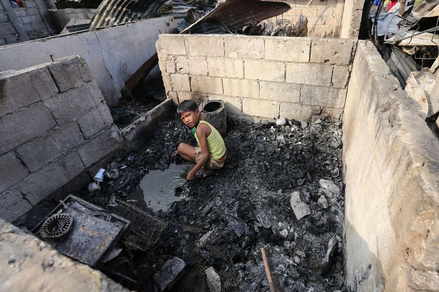 A Filipino boy searching for salvageable materials after the fire.