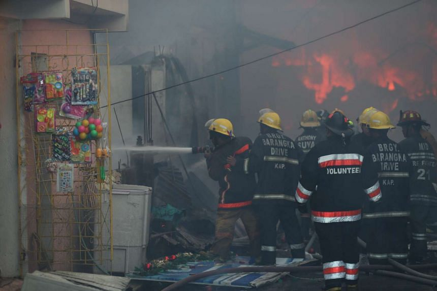 Filipino firefighters battling to contain the fire in Mandaluyong City, east of Manila, Philippines.