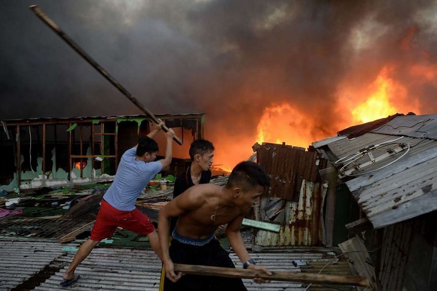 Residents demolishing the walls of a house to help firefighters in their efforts to extinguish the fire.