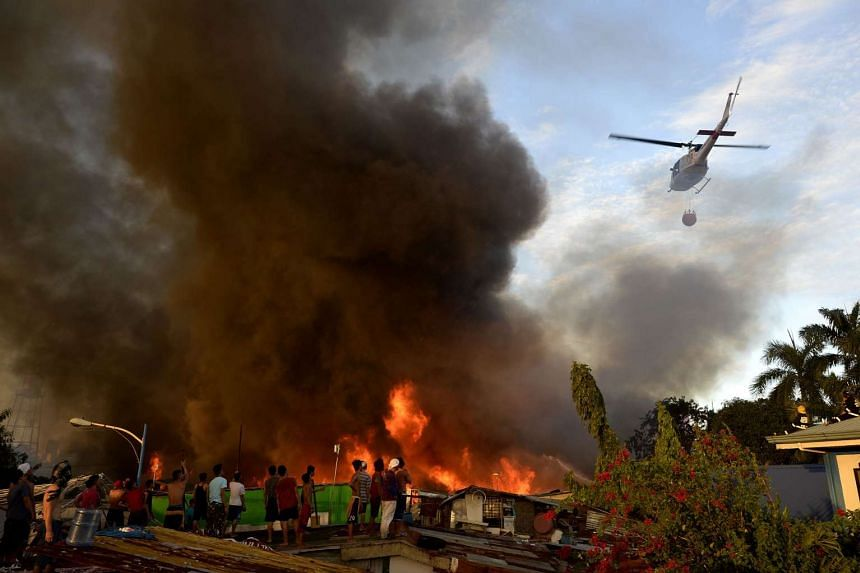 Residents looking at a helicopter extinguish the fire on Nov 25, 2015.
