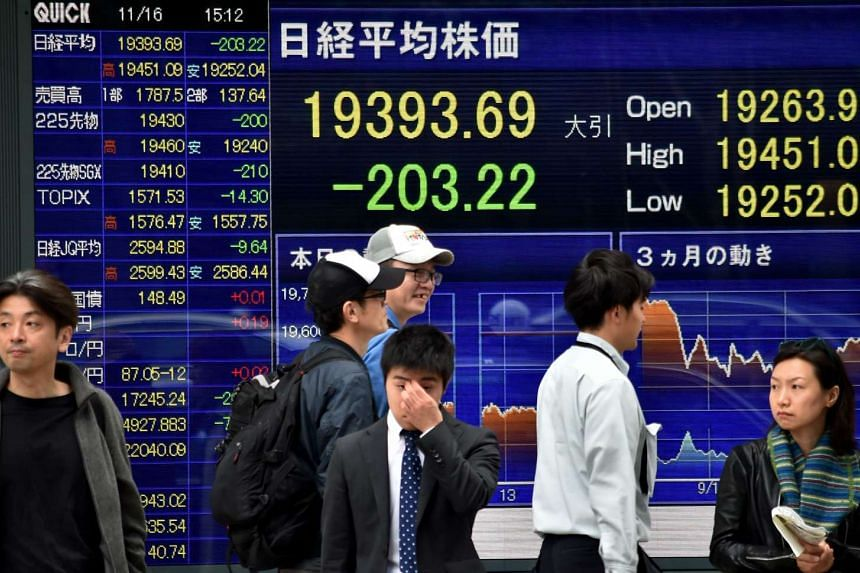 Pedestrians walking past a share prices board of the Nikkei 225 at the Tokyo Stock Exchange on Nov 16, 2015.