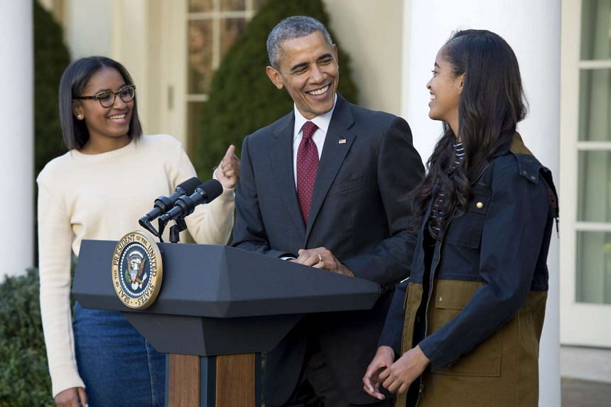 US President Barack Obama (centre) delivering remarks before pardoning two California-raised turkeys. Standing beside him are his daughters Sasha (left) and Malia (right)