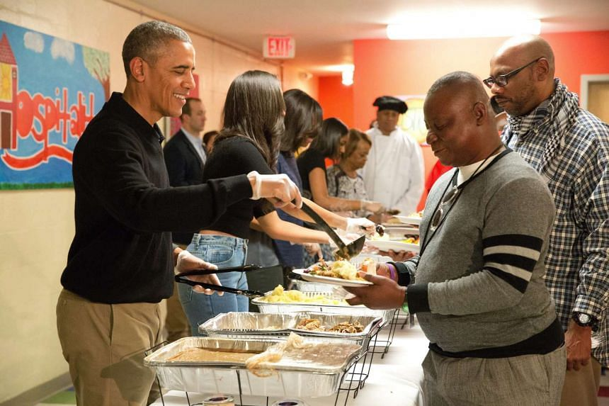 US President Barack Obama (left) and his family serving Thanksgiving meals to the homeless and at-risk veterans at Friendship Place, in Washington DC, US, on Nov 25, 2015.