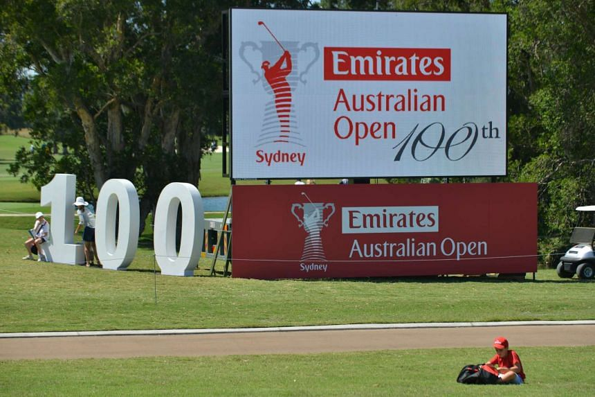 A boy sitting at the side of the fairway in front of a sign for the Australian Open golf tournament on Nov 25, 2015.