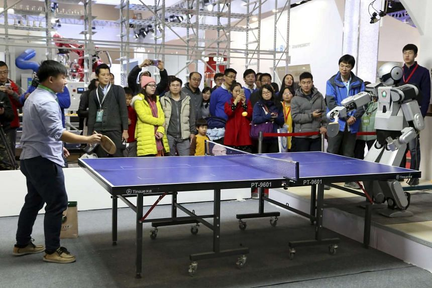 A robot taking on a human at table tennis during a demonstration at the World Robot Conference in Beijing. The automation push has support at the highest levels of China's government.