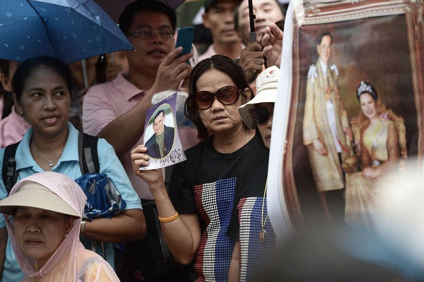 Supporters of Thai nationalist monk Buddha Issara (not pictured) hold portraits of Thai King Bhumibol Adulyadej and Queen Sirikit during a protest at a park in Bangkok on Oct 1, 2015.
