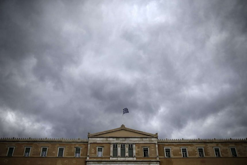 A Greek national flag flutters atop the parliament building in Athens, Greece.