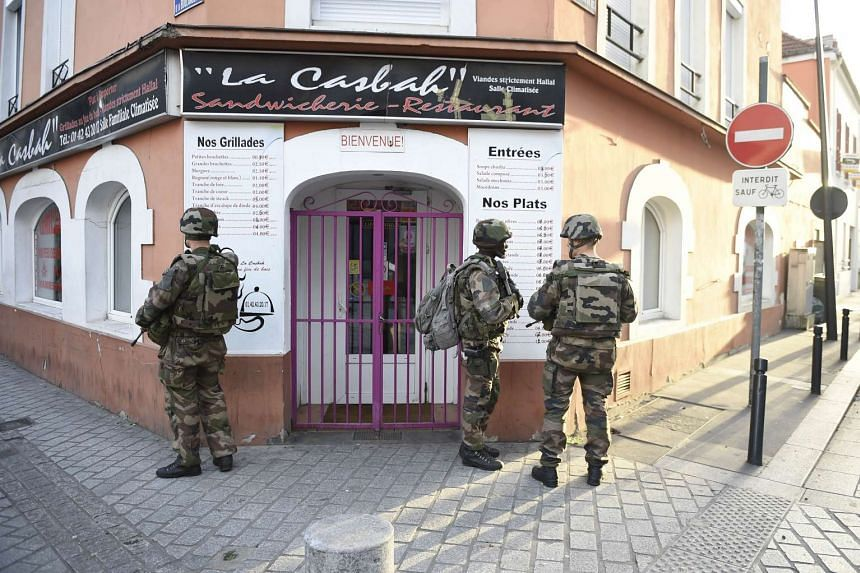 Soldiers stand guard in the northern Paris suburb of Saint-Denis city center, on Nov 18, 2015.