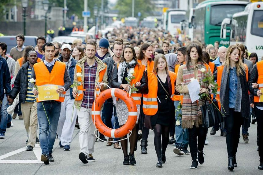 Protesters march during a silent rally in support of migrants and refugees in The Hague on Sept 12, 2015.
