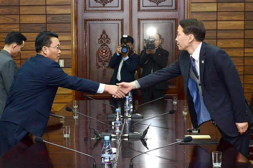 South Korean chief delegate Kim Ki-Woong (right) shakes hands with his North Korean counterpart Hwang Chol at the truce village of Panmunjom in the Demilitarized Zone separating the two Koreas on Nov 26, 2015.