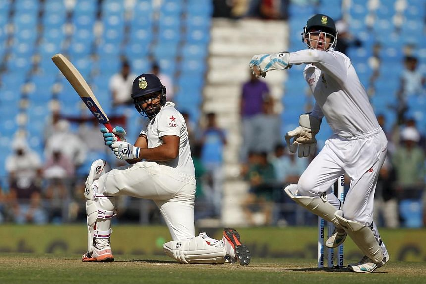 India's Rohit Sharma (left) plays a shot past South Africa's wicketkeeper Dane Vilas during the second day of their third test cricket match in Nagpur, India, on Nov 26, 2015.