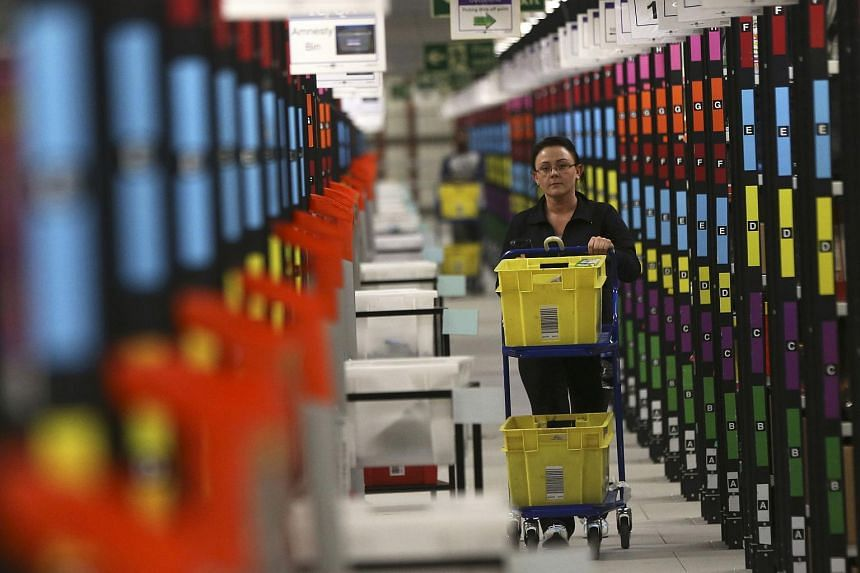 A worker collecting orders during Black Friday deals week at an Amazon fulfilment centre in Hemel Hempstead, Britain, on Nov 25.