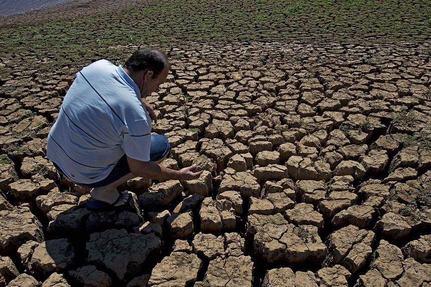 The effects of climate change are seen in this Aug 19, 2014, file photo of cracked ground in an area which used to be underwater at the Jaguari dam in Brazil.