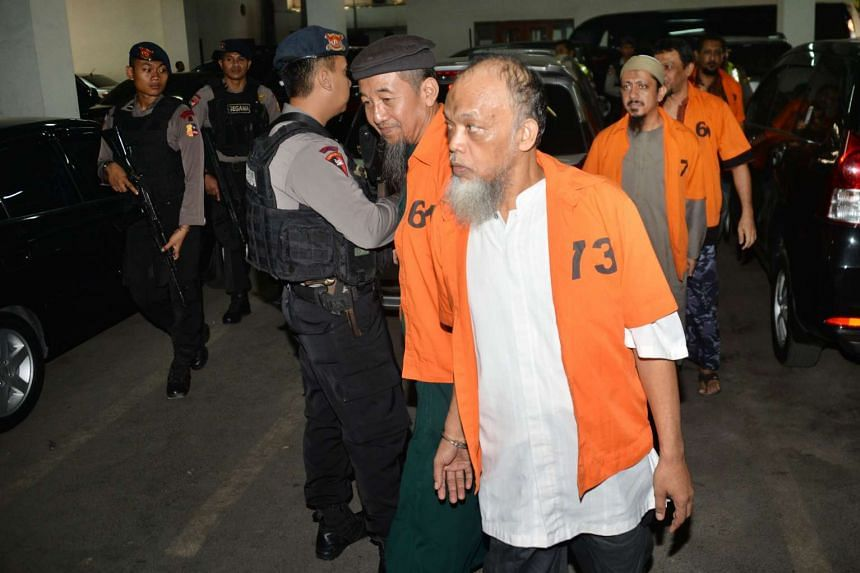 Muhammad Basri (front), an Indonesian with suspected links to ISIS, and other terror suspects arrive for their first trial at the West Jakarta court on Oct 20, 2015.