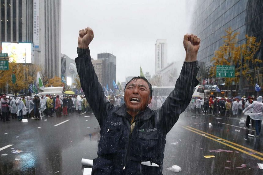 A protester drenched by a police water cannon at a rally in Seoul on Nov 14.