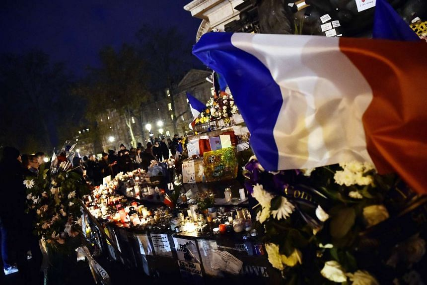 A French flag flutters over candles and flowers as people gather at Place de la Republique in Paris to pay tribute to the victims of the Nov 13 terror attacks, on Nov 22.