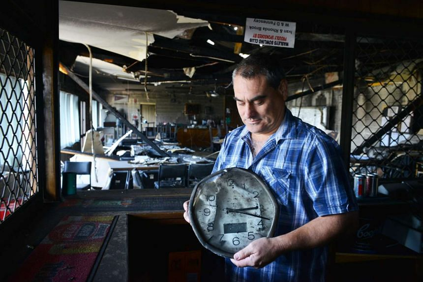 Wasleys Bowling Club Secretary Brad McDougall holding a clock destroyed by fire in South Australia on Nov 26.