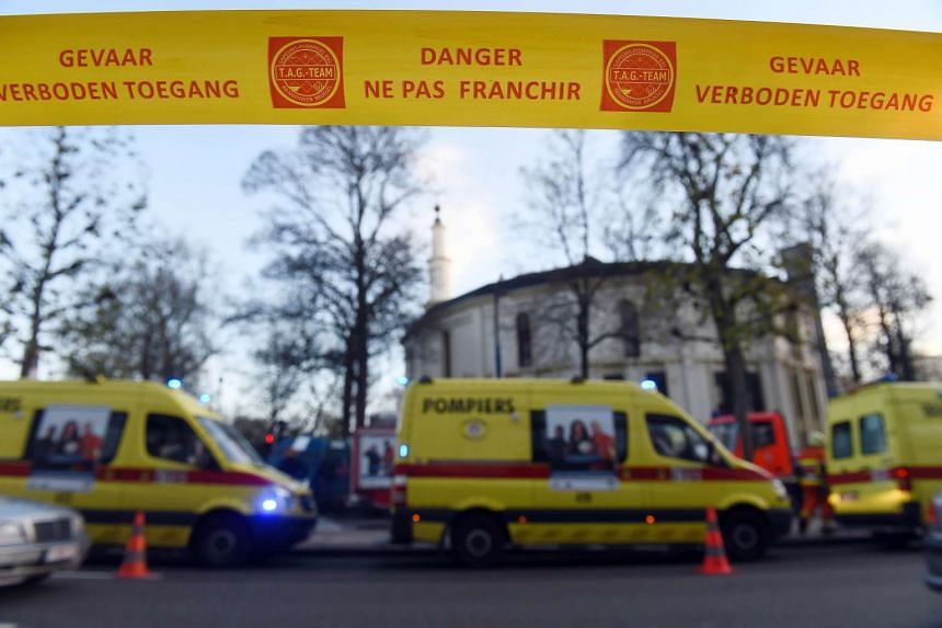 Security personnels and ambulances are in position around Brussels' Great Mosque in Brussels on Nov 26, 2015. The Great Mosque of Brussels was evacuated and 11 people decontaminated after the discovery of a suspicious package containing white powder.