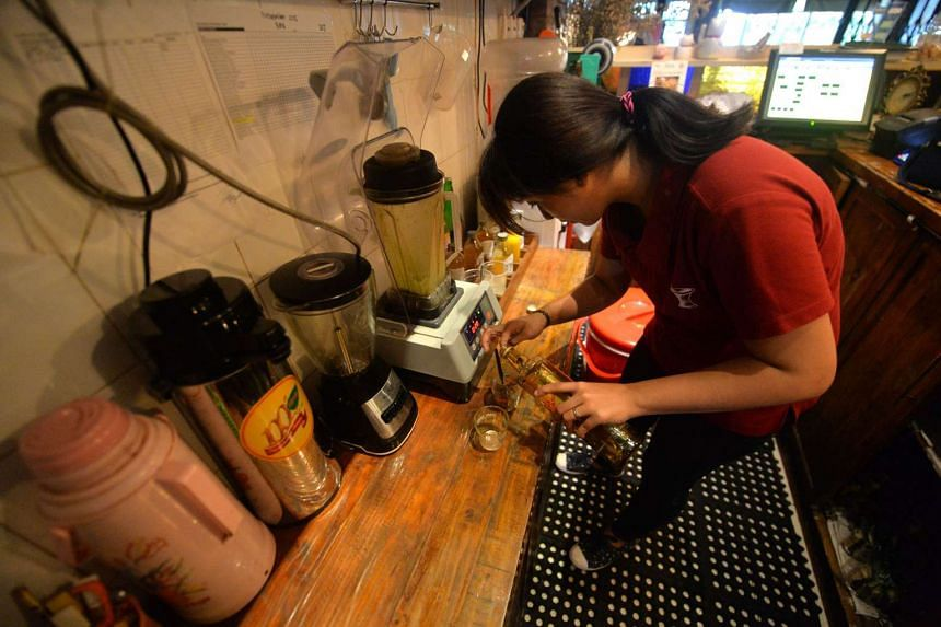 """A cafe employee preparing a drink of traditional Indonesian herbal medicine, known as """"jamu"""", for a customer in Jakarta on Nov 19."""