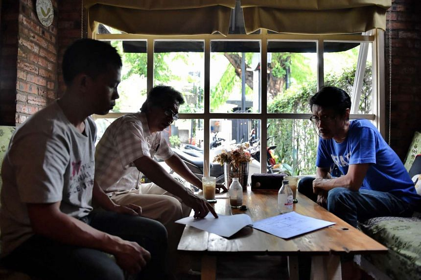 """Customers at a cafe that serves traditional Indonesian herbal medicine, known as """"jamu"""", in Jakarta."""