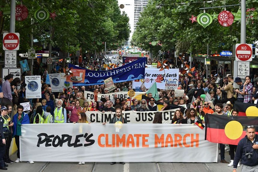 People march along a road during a climate change rally in Melbourne on Nov 27, 2015.